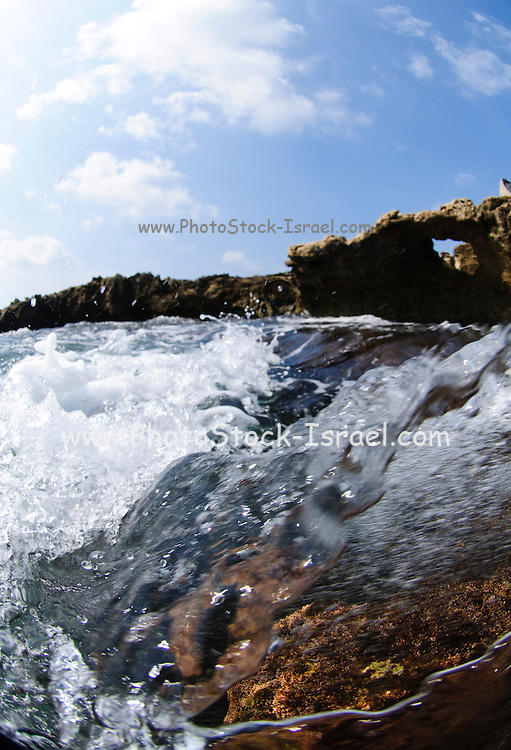 Water abstracts - close up of waves breaking over rocks on a shore