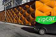 A renred Zipcar drives past the temporary renovation hoarding of luxury brand Louis Vuitton in New Bond Street, on 25th February 2019, in London, England.