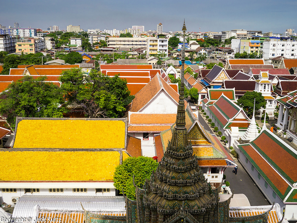 """17 MAY 2013 - BANGKOK, THAILAND: The roofline of Wat Arun with the Thonburi section of Bangkok behind it. Wat Arun is a Buddhist temple (wat) in the Bangkok Yai district of Bangkok, Thailand, on the west bank of the Chao Phraya River. The full name of the temple is Wat Arunratchawararam Ratchaworamahavihara. The outstanding feature of Wat Arun is its central prang (Khmer-style tower). It may be named """"Temple of the Dawn"""" because the first light of morning reflects off the surface of the temple with a pearly iridescence. Steep steps lead to the two terraces. The height is reported by different sources as between 66,80 m and 86 m. The corners are surrounded by 4 smaller satellite prangs. The prangs are decorated by seashells and bits of porcelain which had previously been used as ballast by boats coming to Bangkok from China. The central prang is topped with a seven-pronged trident, referred to by many sources as the """"trident of Shiva"""". Around the base of the prangs are various figures of ancient Chinese soldiers and animals. Over the second terrace are four statues of the Hindu god Indra riding on Erawan. The temple was built in the days of Thailand's ancient capital of Ayutthaya and originally known as Wat Makok (The Olive Temple). In the ensuing era when Thonburi was capital, King Taksin changed the name to Wat Chaeng. The later King Rama II. changed the name to Wat Arunratchatharam. He restored the temple and enlarged the central prang. The work was finished by King Rama III. King Rama IV gave the temple the present name Wat Arunratchawararam. As a sign of changing times, Wat Arun officially ordained its first westerner, an American, in 2005. The central prang symbolizes Mount Meru of the Indian cosmology. The satellite prangs are devoted to the wind god Phra Phai.     PHOTO BY JACK KURTZ"""