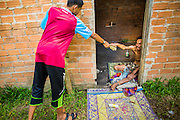 29 OCTOBER 2012 - MAYO, PATTANI, THAILAND:   A neighborhood boy brings food to a patient at the Bukit Kong home in Mayo, Pattani. The home opened 27 years ago as a ponoh school, or traditional Islamic school, in the Mayo district of Pattani. Shortly after it opened, people asked the headmaster to look after individuals with mental illness. The headmaster took them in and soon the school was a home for the mentally ill. Thailand has limited mental health facilities and most are in Bangkok, more than 1,100 kilometers (650 miles) away. The founder died suddenly in 2006 and now his widow, Nuriah Jeteh, struggles to keep the home open. Facilities are crude by western standards but the people who live here have nowhere else to go. Some were brought here by family, others dropped off by the military or police. The home relies on donations and gets no official government support, although soldiers occasionally drop off food. Now there are only six patients, three of whom are kept chained in their rooms.  Jeteh says she relies on traditional Muslim prayers, holy water and herbal medicines to treat the residents. Western style drugs are not available and they don't have a medic on staff.   PHOTO BY JACK KURTZ
