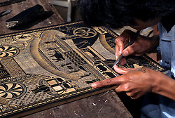 Asia, Indonesia, Sulawesi, Tana Toraja region. Carving images of Tongkonan houses and buffalo, important symbols of wealth, into wood plaque.