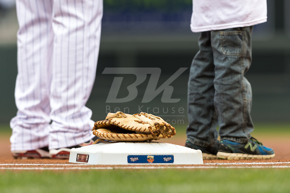 Joe Mauer #7 of the Minnesota Twins stands with a young fan during the national anthem before a game against the Kansas City Royals on April 13, 2014 at Target Field in Minneapolis, Minnesota.  The Twins defeated the Royals 4 to 3.  Photo by Ben Krause