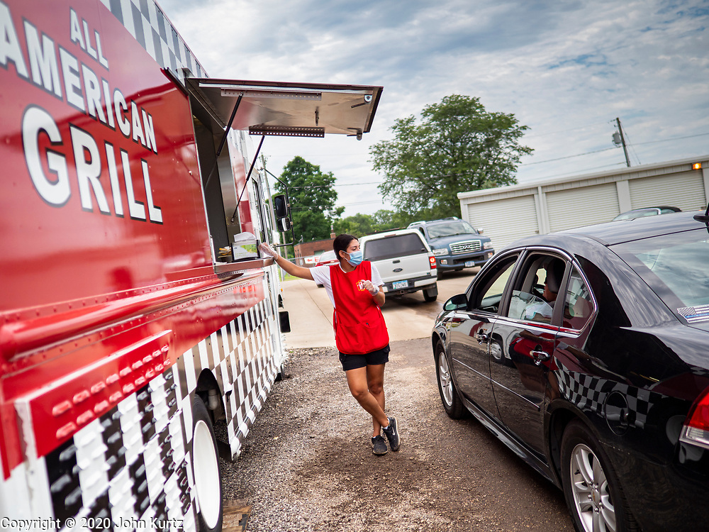 """26 JUNE 2020 - DES MOINES, IOWA: NADINE GARCIA, a worker at the American Grill trailer, waits for a customer's food at Fair Food Friday in Des Moines. The 2020 Iowa State Fair, like many state fairs in the Midwest, has been cancelled this year because of the COVID-19 (Coronavirus) pandemic. The cancellation of the fair left many small vendors stranded with no income. Some of the fair food vendors in Iowa started """"Fair Food Fridays"""" on a property a few miles south of the State Fairgrounds. People drive up and don't leave their cars while vendors bring them the usual midway fare; corndogs, fried tenderloin sandwiches, turkey legs, deep fried Oreos, lemonaide and smoothies. Fair Food Friday has been very successful. The vendors serve 450-500 people per Friday and during the lunch rush people wait in line in their cars 30 - 45 minutes to place an order.      PHOTO BY JACK KURTZ"""
