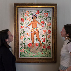 """© Licensed to London News Pictures. 02/10/2018. LONDON, UK. Staff members view """"Erzulie"""", 1961, by Rigau Benoit. Preview of """"Art + Revolution in Haiti"""", an exhibition at The Gallery of Everything in Chiltern Street.  The exhibition, which coincides with Frieze Week, explores when Surrealism arrived in the former slave colony in 1945.  Works from artists from le Centre d'Art d'Haiti and from the personal collection of Andre Breton, the founder of Surrealism, are on display until 11 November 2018.  Photo credit: Stephen Chung/LNP"""