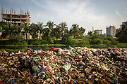 A large pile of rotting waste at a dumping site next to Banani lake in the Karail district of Dhaka on the 24th of September 2018 in Dhaka, Bangladesh.  Environmental pollution next to rivers and lakes is a common sight in Dhaka, polluting water sources that also used for washing and drinking water.