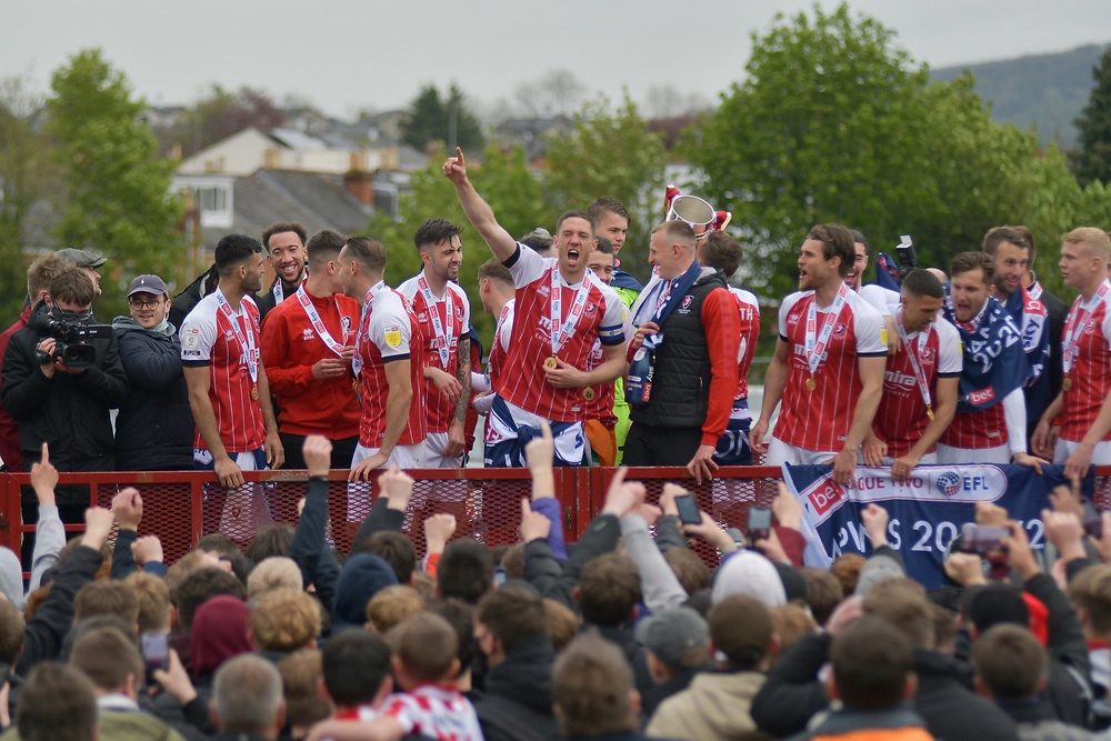 8th May 2021, Cheltenham, England. Cheltenham Town players celebrate as the side won the league and promotion into League one. Fans celebrating outside the stadium as they are unable to attend due to covid 19.