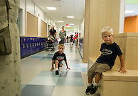 Nolan Rockwell is poised and ready to start Kindergarten as he tours Mill Brook Elementary School along with younger brother Wyatt followed by his parents Mike and Jessamyn and baby sister Bryce during the grand opening held Sunday afternoon.  (Karen Bobotas/for the Concord Monitor)