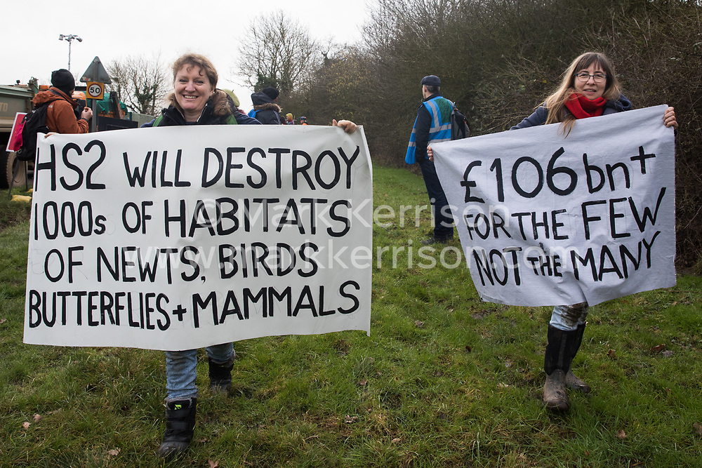 Harefield, UK. 8 February, 2020. Women carry anti-HS2 banners during action by environmental activists from Save the Colne Valley, Stop HS2 and Extinction Rebellion to prevent tree felling works for the high-speed rail project. The activists were successful in preventing any of the scheduled tree felling by HS2 and after an intervention by a police officer all tree felling and strimming work has now been cancelled for the weekend.
