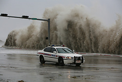 Stock photo of a police cruiser driving along the Galveston seawall with giant waves crashing behind
