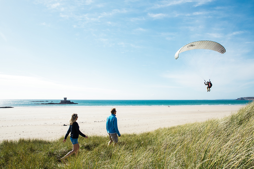 Couple walking through the sand dunes at St Ouen's Bay, Jersey, with a paraglider coming into land overhead, with views out to La Rocco Tower in the sea