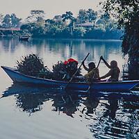 Women carry fodder in a boat on  Phewa Tal Lake, near Pokhara, Nepal.