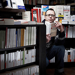 "PARIS, FRANCE. FEBRUARY 2012, 8. Yves Martin, bookseller and owner of his own shop ""Les Buveurs d'Encre"", where the shooting took place. He's holding one of his favorite books of the moment, ""Crooked Letter, crooked letter"" (""Le retour de Silas Jones""). Photo: Antoine Doyen"