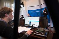 DEU, Deutschland, Germany, Berlin, 14.04.2020: Tobias Raddatz vom RKI an seinem Arbeitsplatz mit Computer, Mischpult und Monitor. Er ist für das Streaming der Pressekonferenz zuständig. Mittels der Software Webex Event wir ein virtueller Konferenzraum geschaffen und Journalisten können ihre Fragen live online stellen. Pressebriefing zum aktuellen Stand der Verbreitung des Coronavirus in Deutschland, Hörsaal des Robert-Koch-Instituts. Im Hintergrund Prof. Dr. Lothar H. Wieler, Präsident Robert Koch-Institut (RKI).