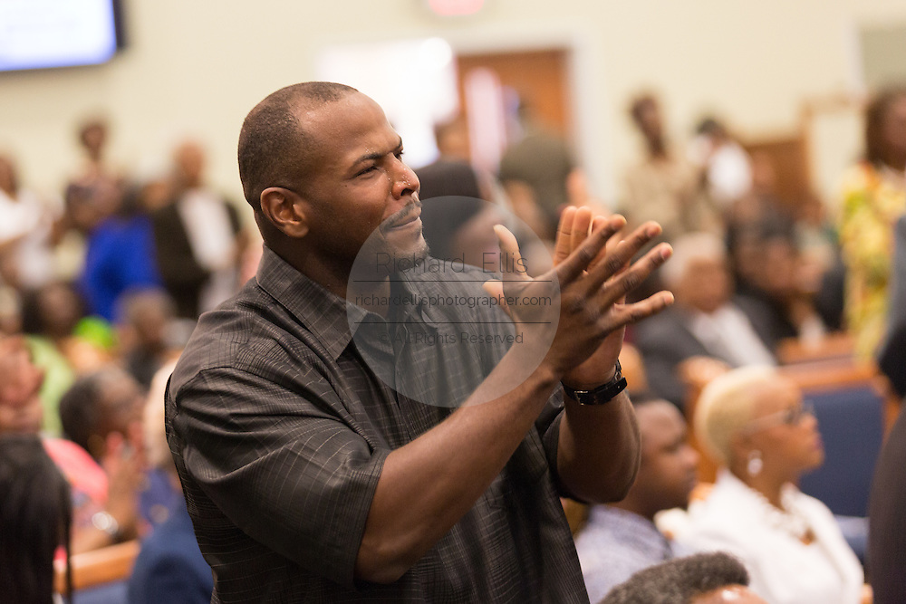 A worshipper reacts during a healing service at Charity Missionary Baptist Church April 12, 2015 in North Charleston, South Carolina. Sharpton spoke following the recent fatal shooting of unarmed motorist Walter Scott police and thanked the Mayor and Police Chief for doing the right thing in charging the officer with murder.