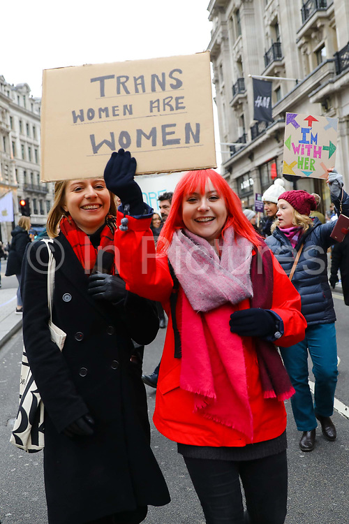 Women with a Trans Women are Women banner at the Bread and Roses Womens March on January 19, 2019 in London, England.  The event was dubbed the Bread and Roses March based on the strikes of the same name by textile workers in Massachusetts in 1912 and Bread and Roses is the title of a poem by American poet James Oppenheim about the strikes.