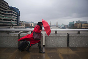 A woman dressed in red struggles with her red umbrella in the rain and wind crossing London Bridge 2nd February 2016.