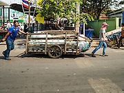 """15 FEBRUARY 2016 - ARANYAPRATHET, SA KAEO, THAILAND: Cambodian porters in Aranyaprathet pull a load of bottled water to the Cambodian side of the border. Thais selling bottled water in the border town of Aranyaprathet, opposite Poipet, Cambodia, have reported a surge in sales recently. Cambodian officials told their Thai counterparts that because of the 2016 drought, which is affecting Thailand and Cambodia, there have been spot shortages of drinking water near the Thai-Cambodian and that """"water shortages in Cambodia had prompted people to hoard drinking water from Thailand.""""     PHOTO BY JACK KURTZ"""