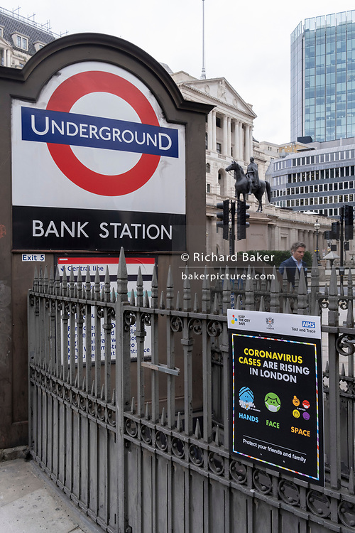 As the UK government tells the nation to prepare for the worst two weeks of the Coronavirus pandemic, a warning aimed at the population to stay at home and minimise contact with others, but in the week when new vaccination centres are opening, is a warning at Bank underground station, for the public to stay safe, on 11th January 2021, in the City of London, England.