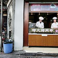 China,Shanghai ,maart 2008..Straatbeeld met een typisch Chinees  straateettentje in het oude traditionele Shanghai.