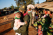 Soldiers with babies in the village at the base of the mountain, near the frontline, 1km from the Thai border nearby Prasat Preah Vihear temple situated in the Dângrêk Mountains..Touth Koeun, an ex-Khmer Rouge child soldier turned midwife and trainer, is on the frontline again, but this time campaigning on maternity issues, in Preah Vihear province, Cambodia. The country experiences an extraordinarily high incidence of infant and maternal mortality. The Preah Vihear province, in Cambodia's north, bordering on the Thai border, can be described as an outback rural area, villages often many hours away from a health centre or clinic, and sometimes near the frontline where soldiers and their families are living. Here, Touth Kouen, a locally much respected pioneer and experienced in maternity issues, trains indigenous women, known as 'Traditional Birth Attendants' (TBA's), correct procedures to assist midwives and nurses, to give direct support to mothers and their babies, during ante and post natal periods. Traditional bush medicine and spiritual practices by 'Kruu' bush doctors, involving the killing of endangered species, gathering herbs and plants, whose burnt remains are often ground up into unhealthy potions, and fed to mothers as miracle cures, and postpartum heating, can cause illness and death. The Kruu, and local people in general need to be re-educated, so as to create a healthy nurturing environment for mothers and their babies. Preah Vihear Province, Cambodia