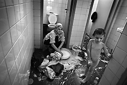 Mirza Khawaji washes clothes while her niece Yousra Kahwaji, 3, waits to be bathed in the bathroom of the Furn Al Shibak Secondary Public School for Girls, located on the outskirts of the southern suburbs of Beirut, Lebanon July 20, 2006.