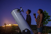 A couple looking at the sky through a telescope while drinking a glass of wine, with Monsaraz village on lite on the top of the hill, in the Alentejo region, in Portugal.