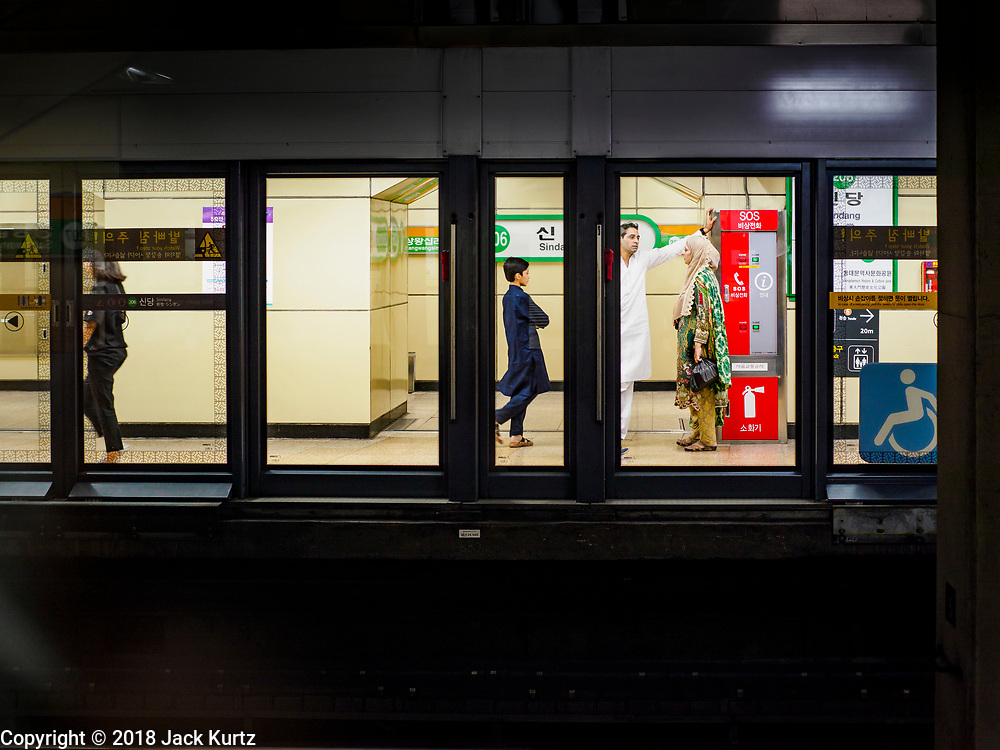 15 JUNE 2018 - SEOUL, SOUTH KOREA: A Muslim family in a subway station after Eid services at Seoul Central Mosque on Eid al Fitr, the Muslim Holy Day that marks the end of the Holy Month of Ramadan. There are fewer than 100,000 Korean Muslims, but there is a large community of Muslim immigrants in South Korea, most in Seoul. Thousands of people attend Eid services at Seoul Central Mosque, the largest mosque in South Korea.    PHOTO BY JACK KURTZ