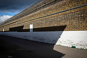 The perimeter wall guarding Her Majesty's Prison Pentonville, London, United Kingdom.  The wall is a tall brick wall and is part of the original prison complex structure. It has two layers of razor wire fence for added security.  The shadow of one of the Prison Wings is cast over the wall. (Photo by Andy Aitchison)