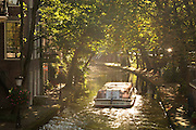 Een rondvaartboot vaart over de Oudegracht in Utrecht.<br /> <br /> A boat trip boat is cruising over the canals in Utrecht