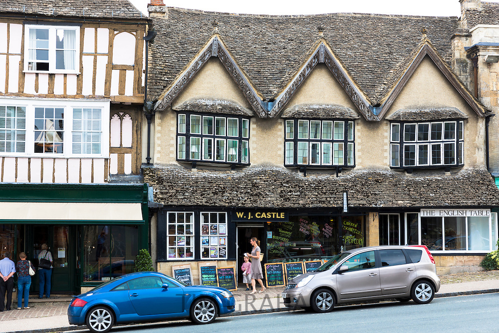 Quaint butcher and cheese shop, medieval and Tudor architecture in famous Burford High Street, The Cotswolds, Oxfordshire, UK