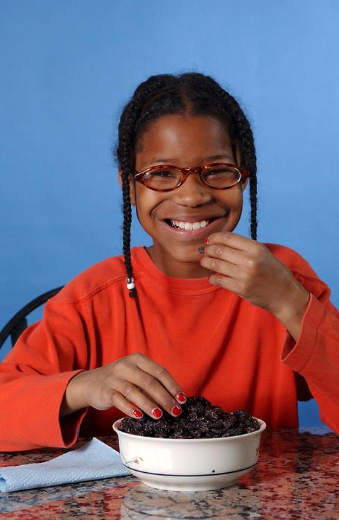 African-American girl (10) eats healthy raisins. Model Released. ©Bob Daemmrich