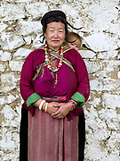 Portrait of a Brokpa woman wearing her traditional clothing carrying her grand-daughter outside the temple on an 'auspicious day' in the remote village of Merak in Eastern Bhutan. The Brokpa, the semi-nomads of the villages of Merak and Sakteng are said to have migrated to Bhutan a few centuries ago from the Tshona region of Southern Tibet. Thriving on rearing yaks and sheep, the Brokpas have maintained many of their unique traditions and customs. Their distinctive hat known as 'tsipee cham' is made of yak felt with long twisted tufts, said to keep the rain from running onto their faces.