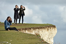 © Licenced to London News Pictures. 30-09-17. Birling Gap, East Sussex. Tourists take perilous selfies on the crumbling cliff edge of the Seven Sisters at Birling Gap, East Sussex, just hours before access is closed due to rapid erosing. Steps that lead down to the beach below the iconic chalk cliffs are being closed on 1st October, years earlier than expected, due to a recent  increase cliff falls. Photo credit: Peter Cripps/LNP
