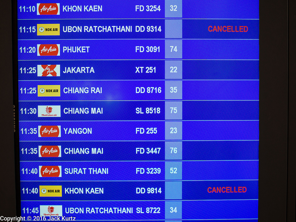 """23 FEBRUARY 2016 - BANGKOK, THAILAND:  A flight status board at Don Mueang International Airport shows some of the cancellations of Nor Air flights. Nok Air, partly owned by Thai Airways International and one of the largest and most successful budget airlines in Thailand, cancelled 20 flights Tuesday because of a shortage of pilots and announced that other flights would be cancelled or suspended through the weekend. The cancellations came after a wildcat strike by several pilots Sunday night cancelled flights and stranded more than a thousand travelers. The pilot shortage at Nok comes at a time when the Thai aviation industry is facing more scrutiny for maintenance and training of air and ground crews, record keeping, and the condition of Suvarnabhumi Airport, which although less than 10 years old is already over capacity, and facing maintenance issues related to runways and taxiways, some of which have developed cracks. The United States' Federal Aviation Administration late last year downgraded Thailand to a """"category 2"""" rating, which means its civil aviation authority is deficient in one or more critical areas or that the country lacks laws and regulations needed to oversee airlines in line with international standards.        PHOTO BY JACK KURTZ"""