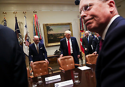 U.S. President Donald Trump (C) arrives for a listening session with health insurance company CEO's, among them Stephen Hemsley CEO's of United Health (R) and Dan Hilferty CEO's of Independence Blue Cross (2L), in the Roosevelt Room of the White House, Washington, DC, February 27, 2017. (Pool / Aude Guerrucci)