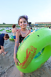 """Young girl with American flag face paint with floating tubes on the Trinity River listening to live music and playing in the river at the """"Rockin' the River"""" July 4th celebration on  the Trinity Trails at the Panther Island Pavilion, Fort Worth, Texas, USA."""