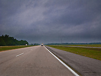 flat farmland along US90 in Louisiana with motion blur in the foreground.