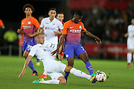Kelechi iheanacho of Manchester city © is tackled by Mike Van der Hoorn of Swansea city.  EFL Cup. 3rd round match, Swansea city v Manchester city at the Liberty Stadium in Swansea, South Wales on Wednesday 21st September 2016.<br /> pic by  Andrew Orchard, Andrew Orchard sports photography.