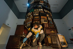 © Licensed to London News Pictures. 24/11/2020. LONDON, UK.  A Tate conservator performs a specialist cleaning of the 8m tall towering sculptural installation called Babel 2001 by Cildo Meireles.  The artwork consists of hundreds of radios of varying ages tuned to a multitude of stations which together produce a cacophony of low, continuous sound. With Tate galleries currently closed during the coronavirus pandemic lockdown, conservators have a chance to provide specialist care for the national collection.  Photo credit: Stephen Chung/LNP