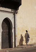 A man in traditional dress walks past the entrance way to a mosque on the edge of the medina in Fes, Morocco