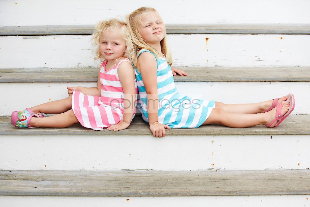 Two Young Girls Sitting Back to Back on Steps