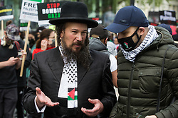 An ultra-Orthodox anti-Zionist Haredi Jew from Neturei Karta UK talks to a man wearing a Palestinian keffiyeh during the National Demonstration for Palestine on 22nd May 2021 in London, United Kingdom. The demonstration was organised by pro-Palestinian solidarity groups in protest against Israel's recent attacks on Gaza, its incursions at the Al-Aqsa mosque and its attempts to forcibly displace Palestinian families from the Sheikh Jarrah neighbourhood of East Jerusalem.