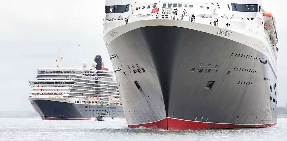 Cunard's fleet gather together in spectacular fashion in Liverpool, its spiritual home, as the company marked its 175th anniversary. Left to right: Queen Elizabeth and Queen Mary 2. The historic lines' three ships, the largest passenger ships ever to muster together on the River Mersey, lined up just 130 metres apart. The vessels lined up three abreast at Liverpool's Pier Head beside its iconic Three Graces: The Royal Liver Building, The Cunard Building and The Port of Liverpool Building. <br /> Picture date Monday 25th May, 2015.<br /> Picture by Christopher Ison. Contact +447544 044177 chris@christopherison.com