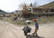 Budge Drive resident Tim Bohan uses a wheelbarrow to retrieve tools from his home Monday after hiking up with a load of groceries. Land owner Jody Burke has allowed his neighbors to cut through his property using a foot trail near the west end of East Gros Ventre Butte.
