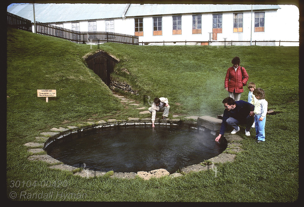 Tourists test temperature of Snorralaug, famous hot springs bath Snorri Sturluson used in 1200s. Iceland