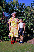 Family portrait full length grandmother and grandson standing in garden, British culture 1967 both wearing slippers