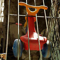South America, Brazil, Rio de Janeiro. A child's Big Wheel hangs in bars in the Favela of Vila Canoas.