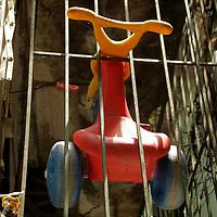 South America, Brazil, Rio de Janeiro. A child's Big Wheel hangs in bars in the Favela of Vila Canoas.