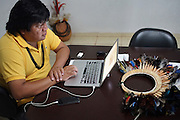 Chief Almir Narayamogo Surui in his office in Cacaol<br /><br />An Amazonian tribal chief Almir Narayamogo, leader of 1350 Surui Indians in Rondônia, near Cacaol, Brazil, with a $100,000 bounty on his head, is fighting for the survival of his people and their forest, and using the world's modern hi-tech tools; computers, smartphones, Google Earth and digital forestry surveillance. So far their fight has been very effective, leading to a most promising and novel result. In 2013, Almir Narayamogo, led his people to be the first and unique indigenous tribe in the world to manage their own REDD+ carbon project and sell carbon credits to the industrial world. By marketing the CO2 capacity of 250 000 hectares of their virgin forest, the forty year old Surui, has ensured the preservation, as well as a future of his community. <br /><br />In 2009, the four clans and 25 Surui villages voted in favour of a total moratorium on logging and the carbon credits project. <br /><br />They still face deforestation problems, such as illegal logging, and gold mining which causes pollution of their river systems