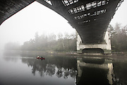 Fog drifted along Seattle's waterfronts and waterways before the sun broke through for a spring-like day.  Two paddlers head down the Montlake Cut below the Montlake Bridge. (Steve Ringman / The Seattle Times)